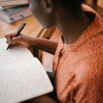 """Photo de femme noire qui écrit pour illustrer la page """"les mots d'Audrey"""""""